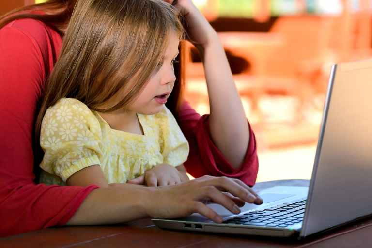 brunette woman in red with girl in yellow on lap before laptop