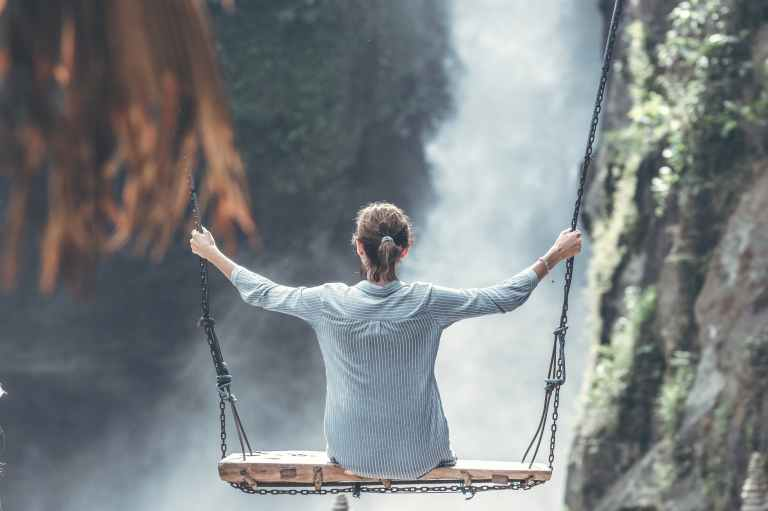 woman riding big swing in front of waterfalls