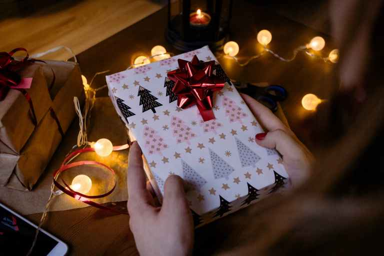 person holding gift box with red ribbon beside string lights