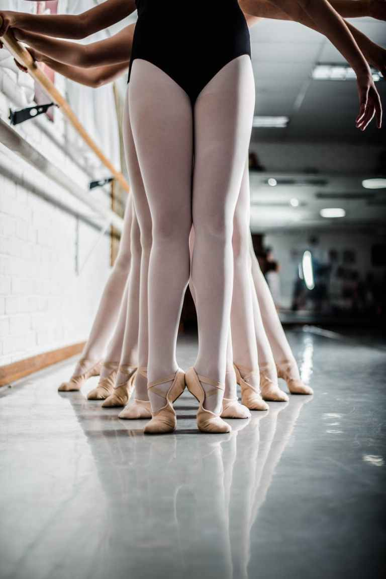 women doing ballet dance near pole