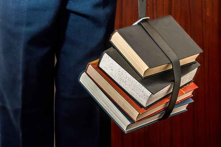 black leather book strapped around four books