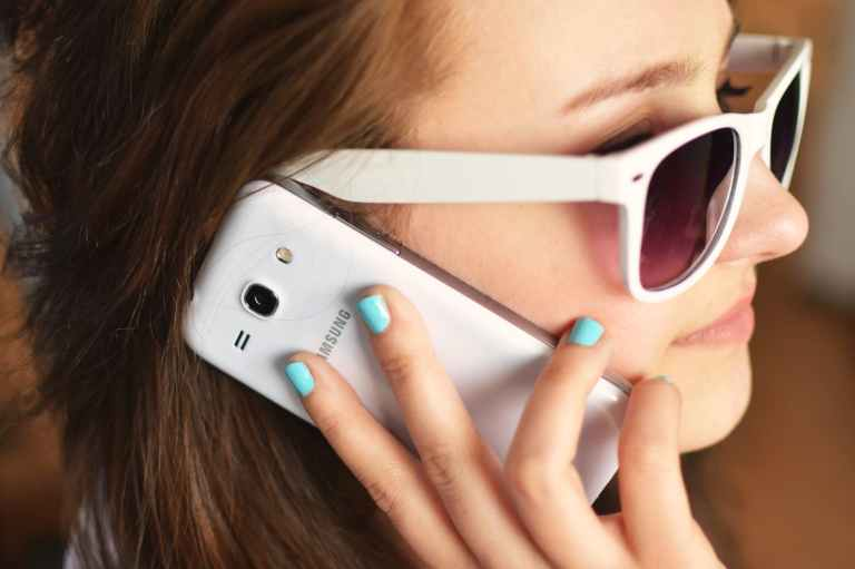 person sunglasses woman smartphone
