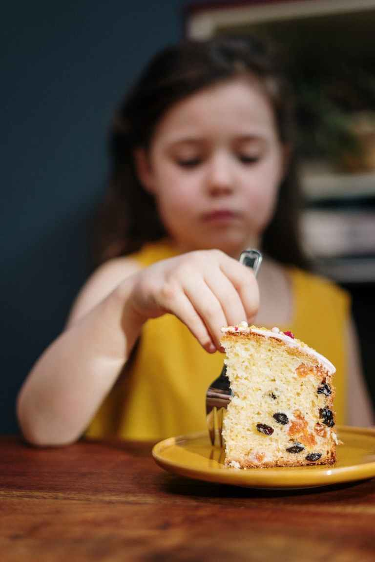 girl in yellow shirt holding sliced of cake
